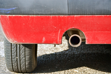 Closeup of the exhaust pipe of an old car that pollute the environment