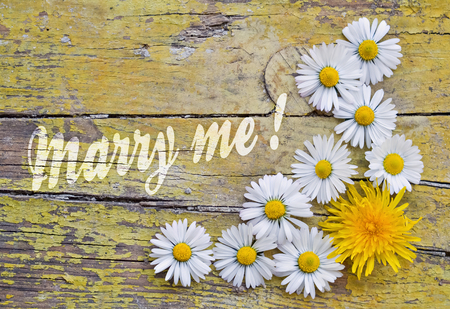 marry: Flowers and text Marry Me written on vintage wooden background Stock Photo