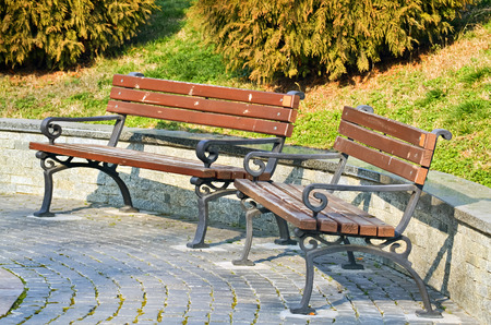 Two empty benches in the city park in a beautiful spring day