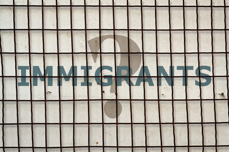 immigrant: Word Immigrant written under a wire fence on vintage background