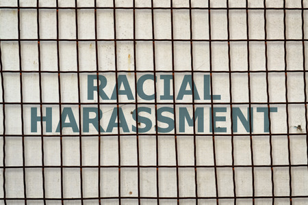 racial: Text Racial Harassment written under a wire fence on vintage background Stock Photo