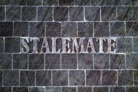 single word: Single word Stalemate written on dark textured background