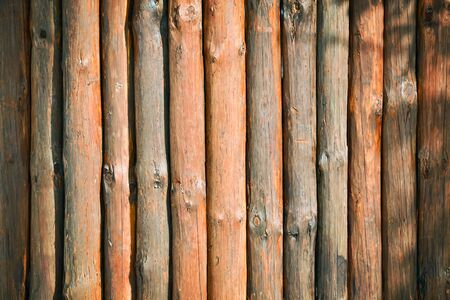 lumber room: Wooden orange background made of tree trunks arranged vertically Stock Photo