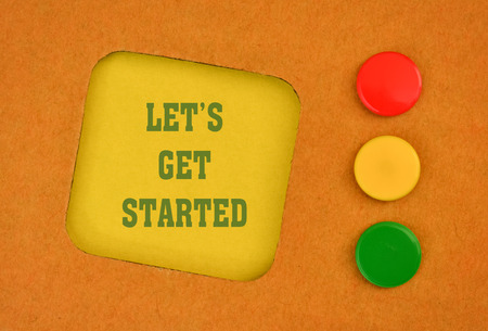 commence: Text Let Get Started written on a yellow sticker and three pins