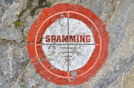 spamming: Single word Spamming in the center of a red circle on textured background
