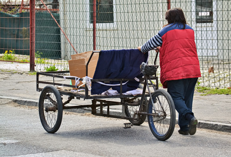 outworn: Poor woman pushing an old three wheel cart on the street