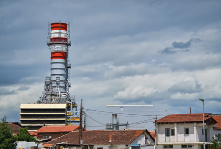 ecological problem: Detail of a factory with pipeline and tall chimney near the village Stock Photo