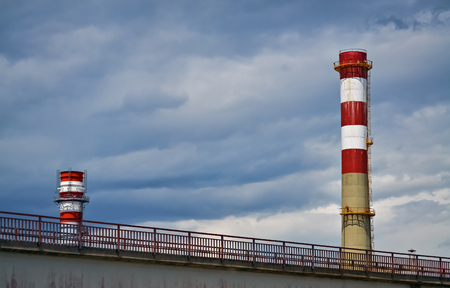 Detail of a factory with two tall chimneys and cloudy sky