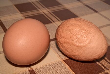 Two eggs on the table one of which is deformed and unhealthy