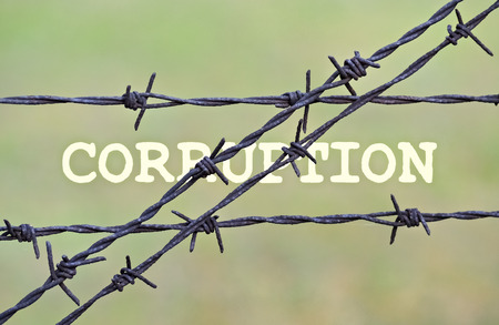 barbs: Word Corruption written under a wire fence with barbs Stock Photo