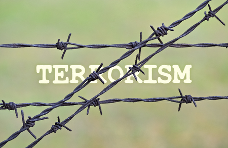 indoctrination: Word Terrorism written under a wire fence with barbs Stock Photo
