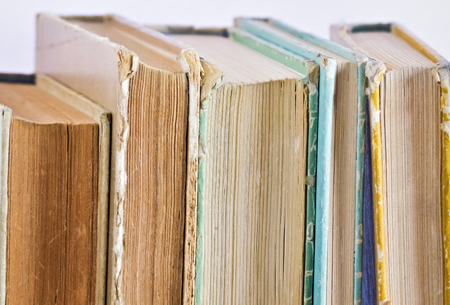 scientific literature: Closeup of several old books vertically placed on the shelf