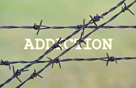 barbs: Word Addiction written under a wire fence with barbs Stock Photo