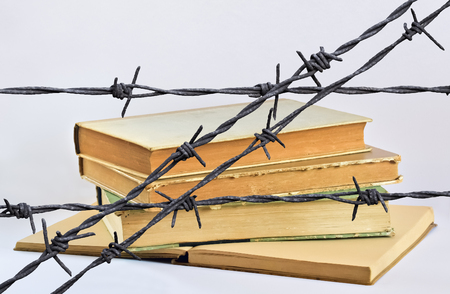 barbs: Stack of several old books behind a wire with barbs
