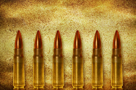 victim war: Six shiny bullets on grunge background arranged vertically Stock Photo