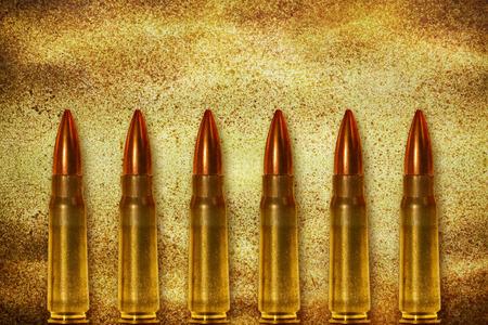 victim war: Six shiny bullets on grunge background arranged vertically Stock Photo