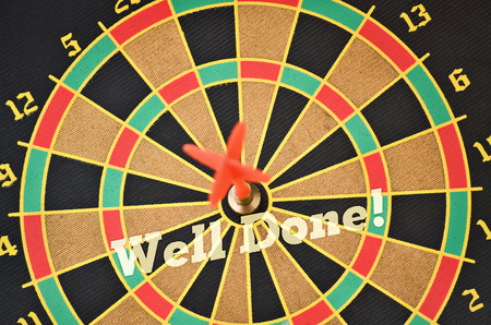 Text Well Done written on the circular target with a plastic feather in the center