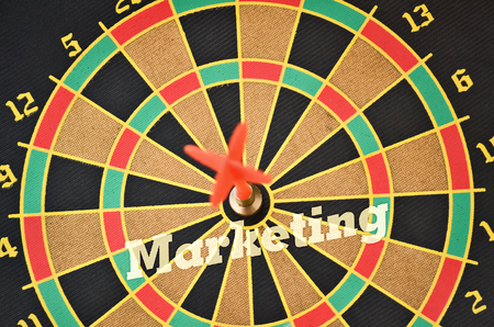 Word Marketing written on the circular target with a plastic feather in the center