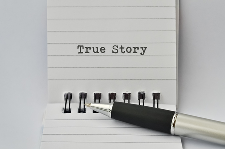 narrate: Text True Story written on paper and a pen