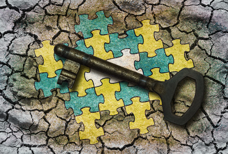 Conceptual illustration - Connected puzzle with one missing part and a key Stock Photo
