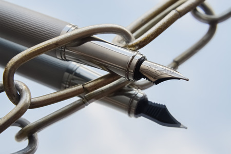 Primo piano di una penna stilografica in argento e una catena