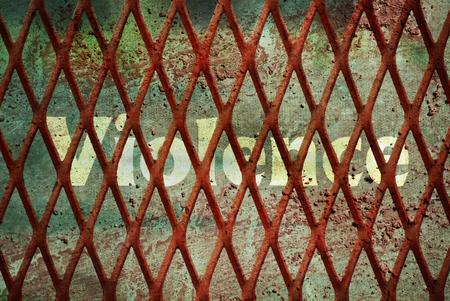 Single word Violence written under rundown rusty fence
