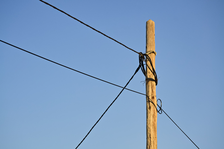 peril: Closeup of an old and dangerous wooden electric pole and the clear sky