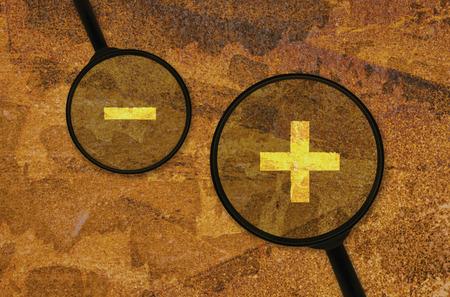 signos matematicos: signos matemáticos para la suma y la resta bajo una lupa Foto de archivo