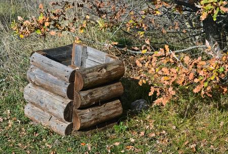 cesto basura: cesta de la basura de madera y hojas secas de naranja en el parque