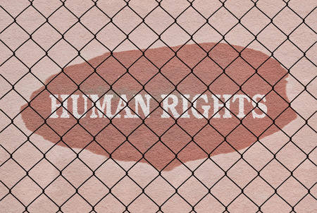 repress: Text Human Rights written under a wire fence