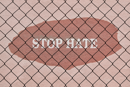 waive: Text Stop Hate written under a wire fence