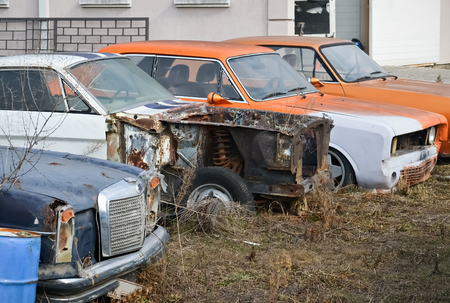 Front part of several old abandoned retro cars in the yard