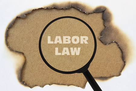 Text Labor Law written under a magnifier on a burnt paper Stock Photo