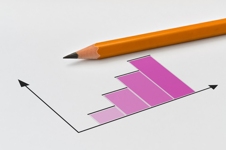 Closeup of a yellow pencil and bar chart on bright background