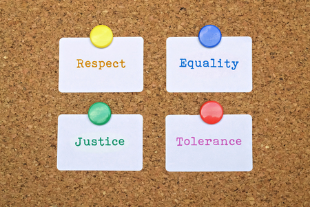bigotry: Words Equality and Justice written on four white stickers pinned on cork board