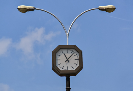 Electric clock on the street with a lamp behind it Stock Photo