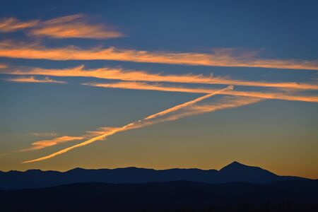 Orange contrails on the sky during the sunset Stock fotó