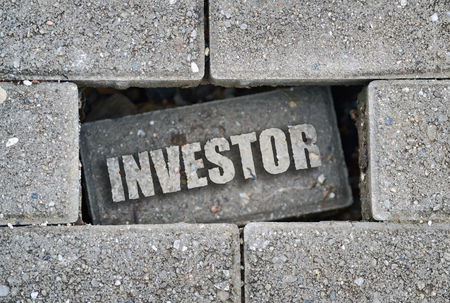 Word Investor written over a broken brick on the pavement Stock Photo