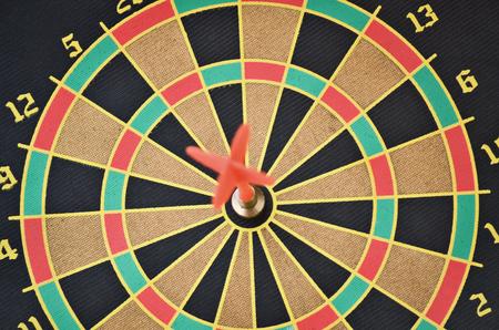 Closeup of a cork dartboard and arrow in the bullseye