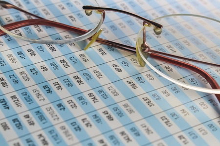 Detail of a spreadsheet and glasses on the table in the office