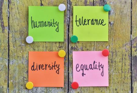 Quattro adesivi con testo scritto a mano sulla tolleranza umana appuntato su fondo di legno