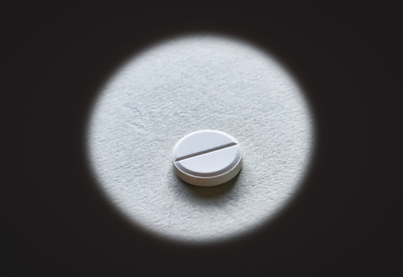 Closeup of a white tablet in the middle of dark circle Stock Photo