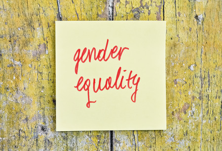Handwritten text Gender Equality on a sticker pinned on wooden background Stock Photo