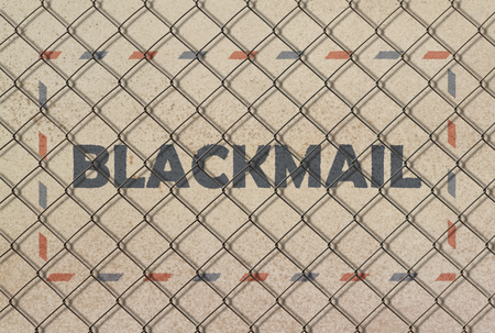 Text Blackmail written under a wire fence on grunge background