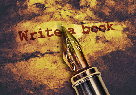 Text Write a Book and a fountain pen on dark golden background