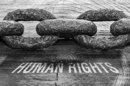 Text Human Rights written on rough wooden background and a thick chain