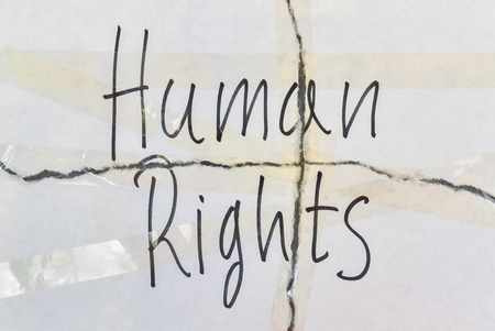 Text Human Rights written on torn paper and glued with scotch tape