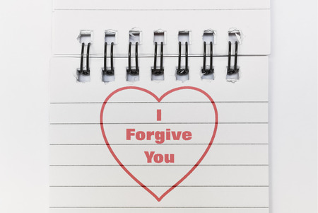 Text I Forgive You and a heart written in red on white paper Stock Photo