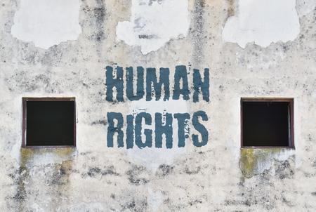 Los derechos humanos de texto escrito en la pared de una antigua cárcel Foto de archivo
