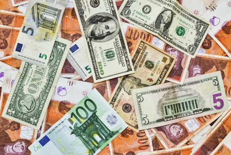 Many banknotes in various currencies scattered on the table Stock Photo